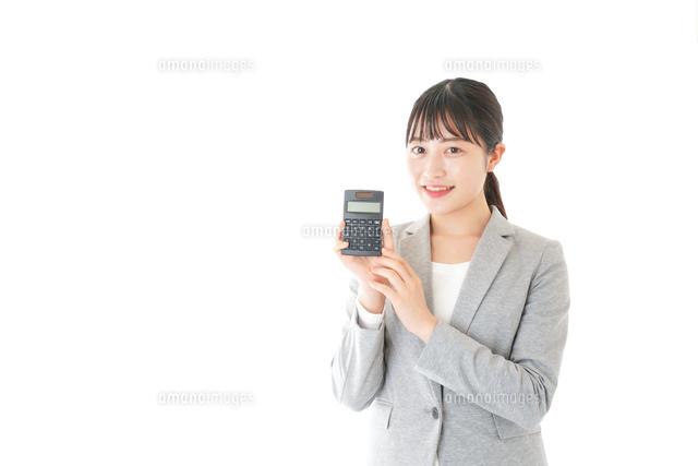 電卓で計算をする若いキャリアウーマンの写真素材 [FYI04727123]