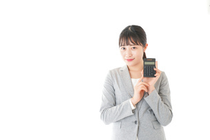 電卓で計算をする若いキャリアウーマンの写真素材 [FYI04727125]