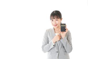 電卓で計算をする若いキャリアウーマンの写真素材 [FYI04727128]