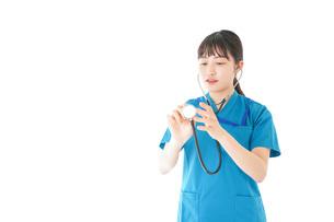 聴診器を使う笑顔の若いナースの写真素材 [FYI04727233]