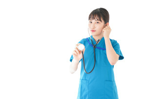 聴診器を使う笑顔の若いナースの写真素材 [FYI04727234]