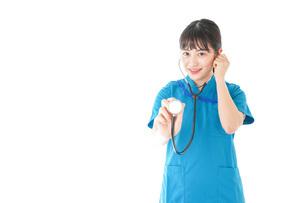 聴診器を使う笑顔の若いナースの写真素材 [FYI04727235]