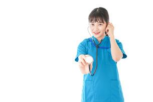 聴診器を使う笑顔の若いナースの写真素材 [FYI04727238]