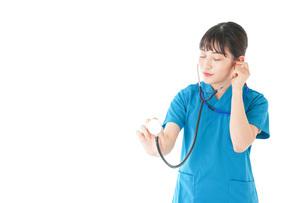 聴診器を使う笑顔の若いナースの写真素材 [FYI04727242]