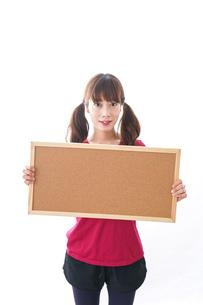 コルクボードを持つ女性の写真素材 [FYI04727431]