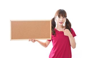 コルクボードを持つ女性の写真素材 [FYI04727437]