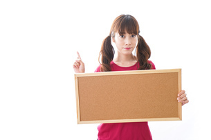 コルクボードを持つ女性の写真素材 [FYI04727440]