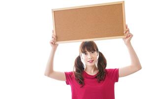 コルクボードを持つ女性の写真素材 [FYI04727442]