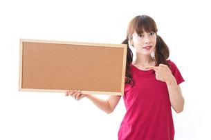 コルクボードを持つ女性の写真素材 [FYI04727444]