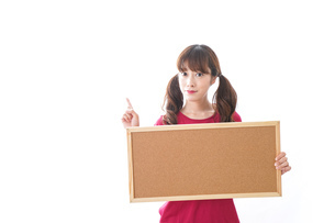 コルクボードを持つ女性の写真素材 [FYI04727446]