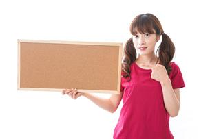 コルクボードを持つ女性の写真素材 [FYI04727449]
