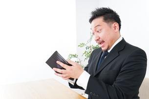 財布を見て驚くビジネスマンの写真素材 [FYI04727524]