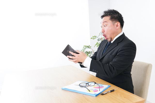 財布を見て驚くビジネスマンの写真素材 [FYI04727526]