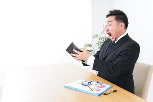 財布を見て驚くビジネスマンの写真素材 [FYI04727527]