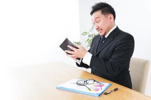 財布を見て驚くビジネスマンの写真素材 [FYI04727529]