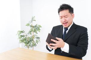 財布を見て驚くビジネスマンの写真素材 [FYI04727530]