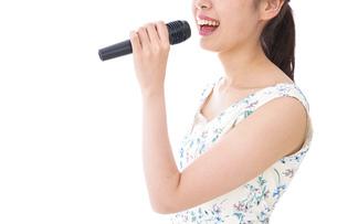 カラオケで歌う若い女性の写真素材 [FYI04727660]