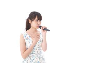 カラオケで歌う若い女性の写真素材 [FYI04727667]