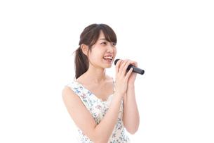 カラオケで歌う若い女性の写真素材 [FYI04727668]