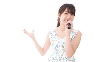 カラオケで歌う若い女性の写真素材 [FYI04727670]