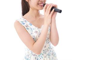 カラオケで歌う若い女性の写真素材 [FYI04727671]
