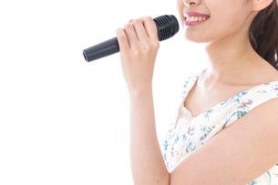 カラオケで歌う若い女性の写真素材 [FYI04727676]
