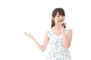 カラオケで歌う若い女性の写真素材 [FYI04727677]
