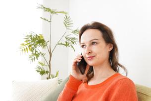 家で通話をする若い女性の写真素材 [FYI04727705]