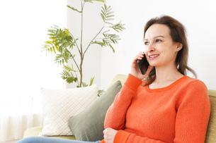家で通話をする若い女性の写真素材 [FYI04727713]