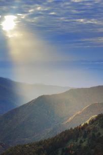 横手山のぞき付近から望む長野市方向の山並みと夕方の光芒の写真素材 [FYI04728576]