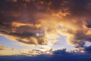 思い出の丘付近から望む雲間の夕日と夕焼けの写真素材 [FYI04728626]