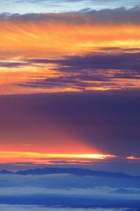 美ヶ原高原美術館付近から望む矢沢峠方向の山並みと朝の光芒の写真素材 [FYI04728628]