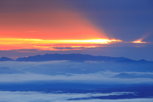 美ヶ原高原美術館付近から望む矢沢峠方向の山並みと朝の光芒の写真素材 [FYI04728629]