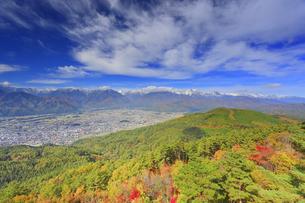 鷹狩山から望む北アルプスの山並みと大町市街と紅葉の樹林の写真素材 [FYI04728688]