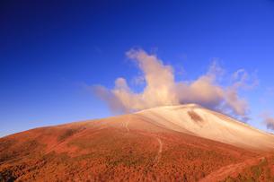 小浅間山から望む朝日に染まる新雪の浅間山と噴煙と山の字状の雲の写真素材 [FYI04728731]