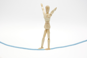 バランスをとりながら綱渡りをするデッサン人形の写真素材 [FYI04728768]