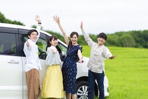 車の前でポーズをとる若者の写真素材 [FYI04728784]