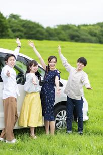 車の前でポーズをとる若者の写真素材 [FYI04728785]