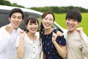 車の前でポーズをとる若者の写真素材 [FYI04728788]