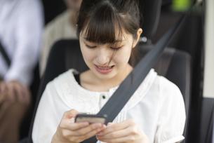 車内でスマホを見る若い女性の写真素材 [FYI04728801]