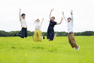 草原でジャンプする若者の写真素材 [FYI04728805]