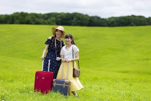草原でスーツケースを持つ女性の写真素材 [FYI04728844]