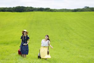 草原でスーツケースを持つ女性の写真素材 [FYI04728845]
