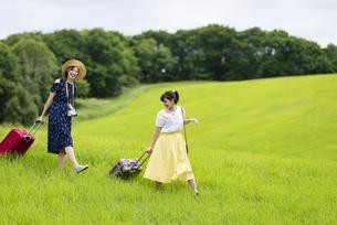 草原でスーツケースを持つ女性の写真素材 [FYI04728846]
