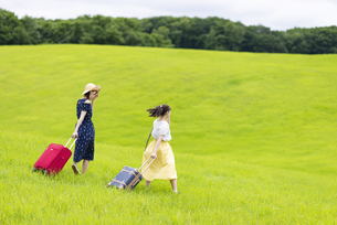 草原でスーツケースを持つ女性の後ろ姿の写真素材 [FYI04728847]