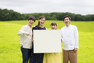 草原でホワイトボードを持つ若者の写真素材 [FYI04728852]