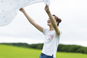 草原で敷物を広げる女性の写真素材 [FYI04728856]
