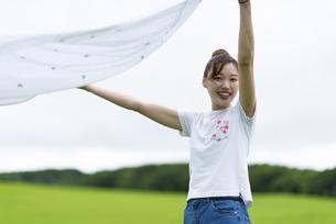 草原で敷物を広げる女性の写真素材 [FYI04728857]