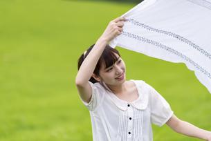 草原で敷物を広げる女性の写真素材 [FYI04728866]