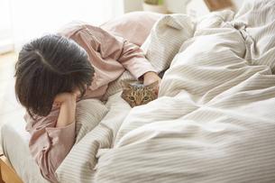 ベッドのうえで猫と戯れる女性の写真素材 [FYI04728875]